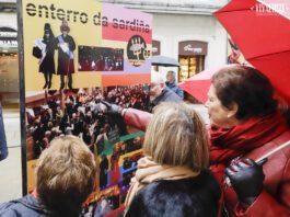 """Xente mirando a exposición """"Asociación Pepe Barreiro, un antes e un despois"""" que pode visistarse estos días na rúa da Raíña"""
